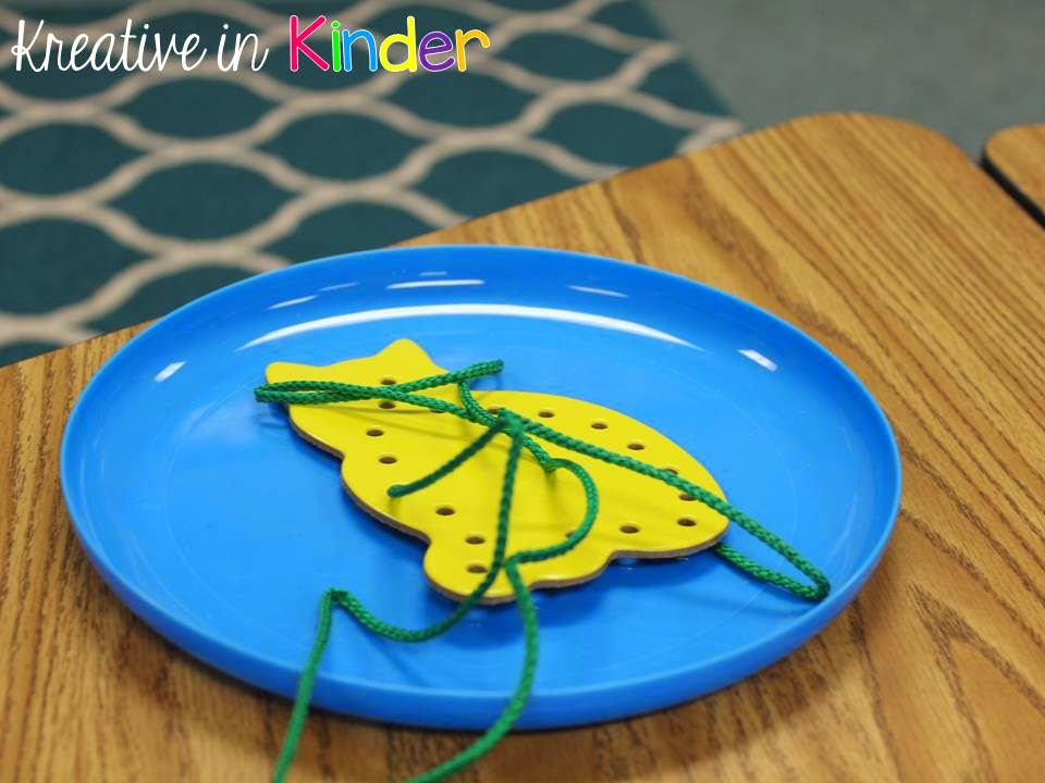 Sitting on a Kindergarten desk is a yellow lacing card shaped like a cat with a green shoelace through it, in a blue frisbee being used as a plate. Lacing cards are used to develop fine motor skills.